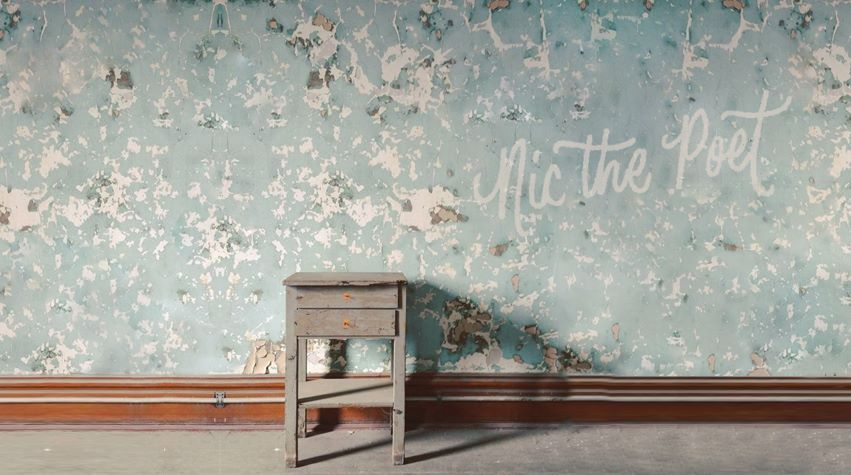 a lone bed side table in a tattered room